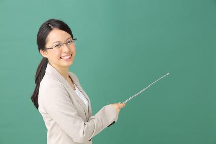 指示棒で指す教師・女性